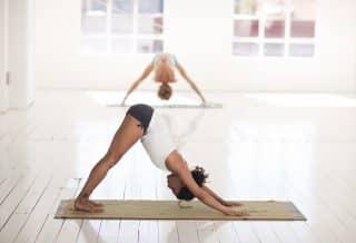 Femme en posture de yoga sur son tapis de yoga antidérapant et bio